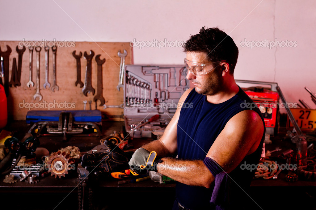 View of a garage mechanic man putting some protective gloves. — Stock Photo #6768729