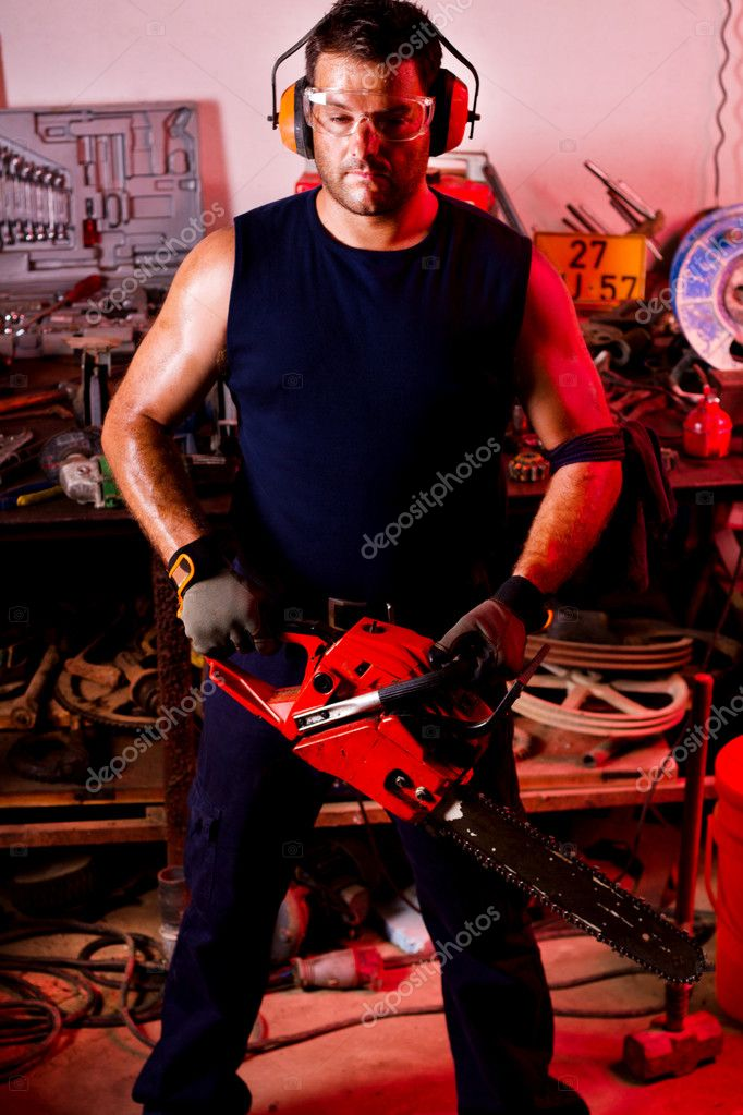 View of a garage mechanic man holding a chainsaw. — Stock Photo #6768799