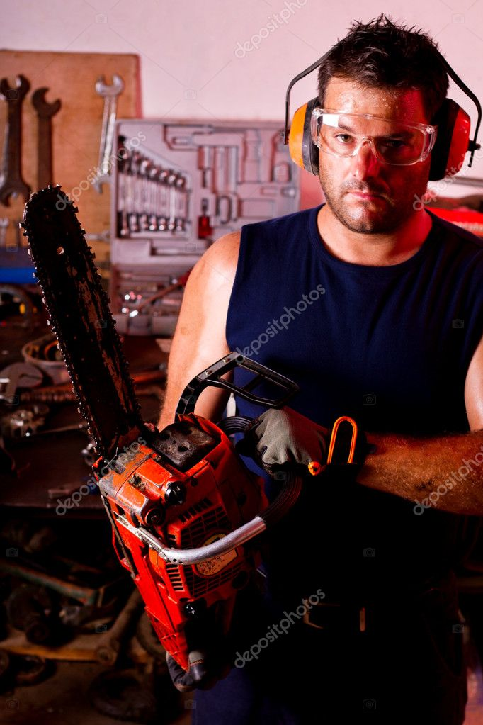 View of a garage mechanic man holding a chainsaw. — Stock Photo #6768810