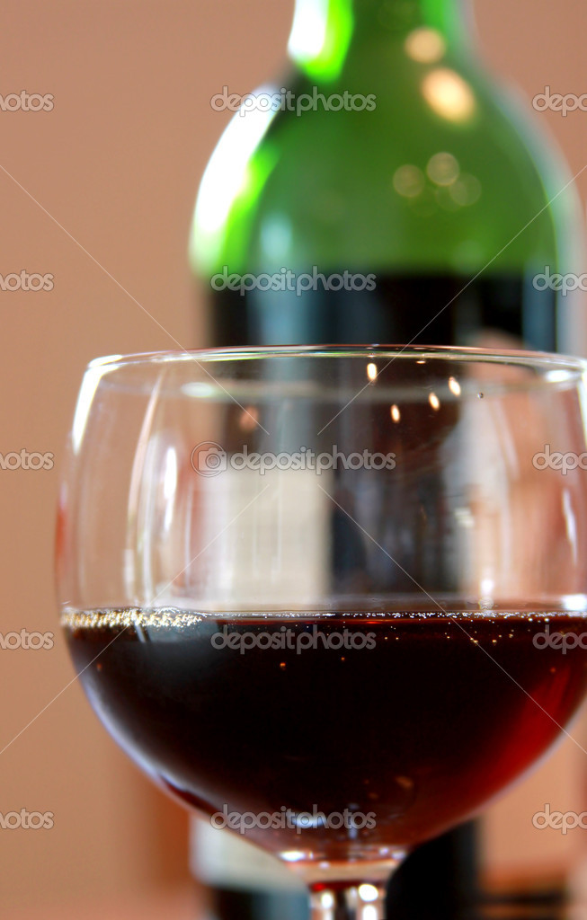 Red wine glass and with background of wine bottle — Stock Photo #6940784