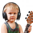 Foto Stock: Little boy with headphones and guitar