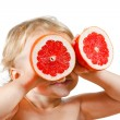 Little boy with a pink grapefruit — Stock Photo