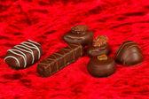 Chocolates en el fondo de terciopelo rojo — Foto de Stock