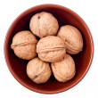 Ceramic bowl full of walnuts isolated on white — Stock Photo