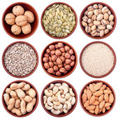 Assortment of nuts and seeds in ceramic bowls isolated on white — Stock Photo