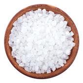 Wooden bowl full of sea salt over white — Stock Photo