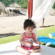 Baby girl in sunglasses on the beach playing getting prepared fo — Lizenzfreies Foto