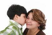Malý chlapec políbit jeho matku na bílém pozadí — Stock fotografie