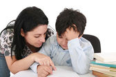 Mother helping with homework to her son indoor — Стоковое фото