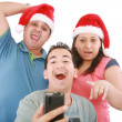 Young friends looking shocked at cell phone with Christmas hat — 图库照片 #7301137