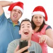 Young friends looking shocked at cell phone with Christmas hat — Stock fotografie