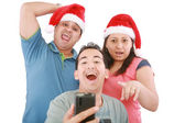 Young friends looking shocked at cell phone with Christmas hat — Stock Photo