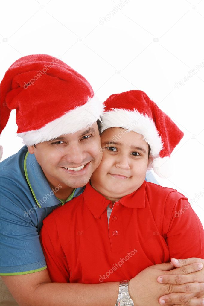 Happy father and son with Christmas hats look to the camera  Stock Photo #7301080