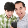 Stock Photo: Young father and son was surprised, having read on mobile phone