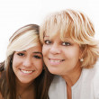 Mother and attractive young daughter smiling happily, looking at — Stock Photo
