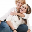 Mother and daughter sitting and laughing on the floor — Stock Photo