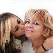 Closeup of young girl kissing her mom isolated on a white backgr — Stock Photo