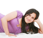 Smiling young woman laying on bed — Stock Photo