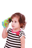 Smiling cute little girl in dress calling by telephone — Stock Photo
