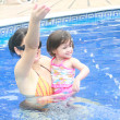 Mother and baby playing in a swimming pool — Stock Photo
