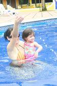 Anne ve bebek yüzme havuzunda oynamayı — Stok fotoğraf