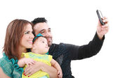 Closeup of happy family smiling over white background taking sel — Stock Photo