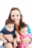 Happy young mother with two babies on a white background. — Stock Photo