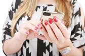 Close shot of woman hand holding a mobile phone typing a sms — Stock Photo