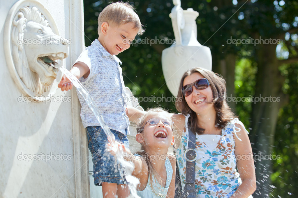 Beautiful Mother with her kids playing with water in fountain  Stock Photo #7067235