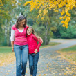 Cute girl with her mother walking in park — Stock Photo #7139379