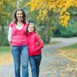Cute girl with her mother walking in park — Stock Photo #7142858