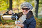 Woman drinks tea in autumn park — Stock Photo
