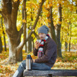 Man drinks tea in autumn park — Stock Photo