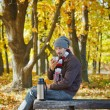 Man drinks tea in autumn park - Stock Photo