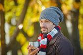 Man drinks tea in autumn park — Stock Photo