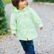 Little girl in green walking park. — Stock Photo