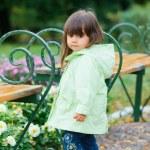 Little girl in green walking park. — Stock Photo #7411521