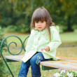 Little girl sitting on a bench in the park — Stock Photo #7428665