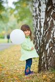 Little girl in green walking park. — Stock Photo