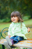 Little girl sitting on a bench in the park — Stock Photo