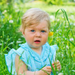 Little girl sitting in the grass in the park — Stock Photo #7474398