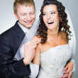 Laughing groom and  bride on grey — Stock Photo