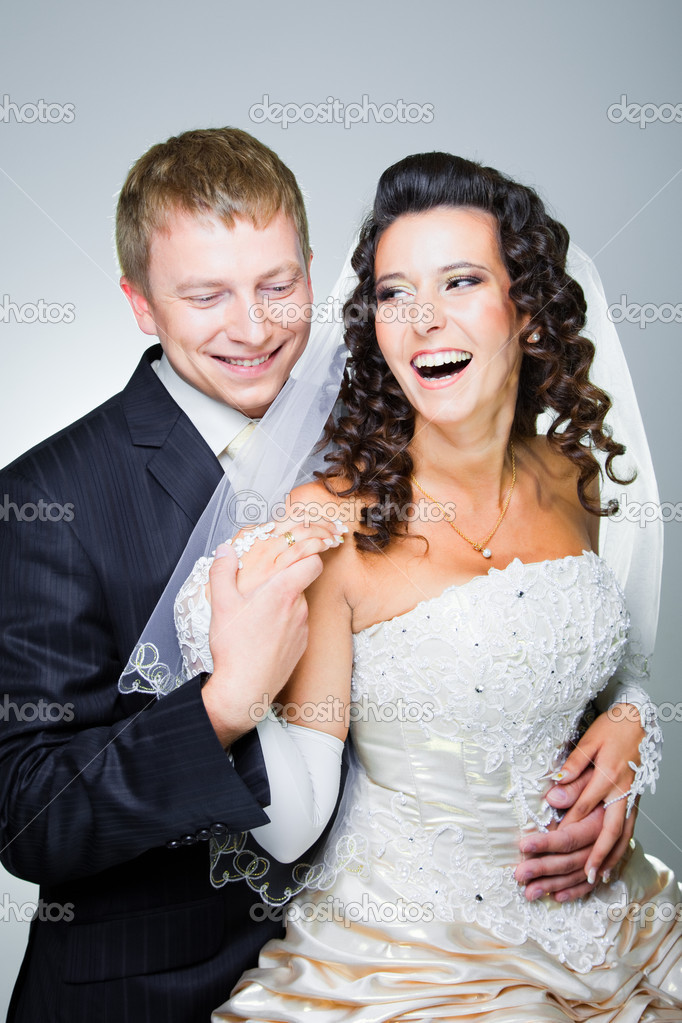 Studio portrait of young elegant laughing just married bride and groom and  embracing on grey background — Stock Photo #6822491