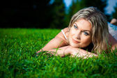 Attractive womanlying on green grass and waiting for dawn — Stock Photo