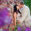 Romantic kiss near old brick wall — Stock Photo