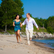 Foto Stock: Enamored couple running along coast of sea