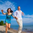 Enamored couple running along the coast of sea — Stock Photo