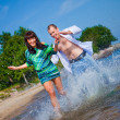 Stock Photo: Enamored couple running along coast of sea