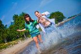 Enamored couple running along the coast of sea — Stock Photo