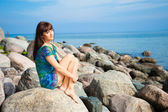 Beautiful brunette girl sitting on beach stones — Stock Photo